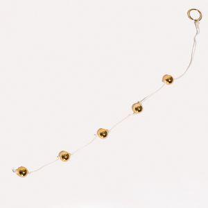 Цепочка из пяти золотистых анальных шариков